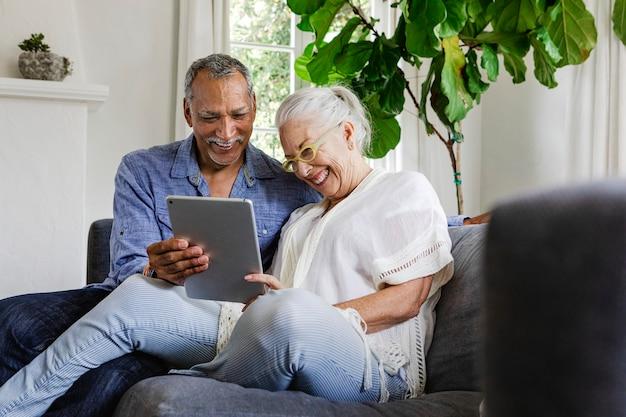 Casal de idosos usando tablet no sofá