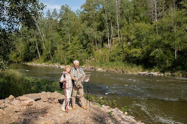Casal de idosos vestindo roupas esportivas em pé à beira do rio da floresta e usando o mapa-guia para encontrar o caminho de volta