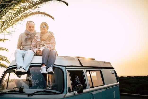Casal de idosos viajantes sentam-se juntos no teto da van e aproveitam o pôr do sol juntos com amor - para sempre e o conceito de férias para viajantes aposentados