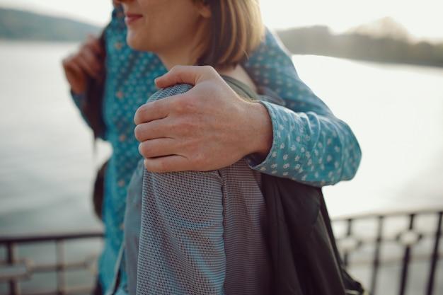 Casal de imagem recortada andando perto do lago com foco na mão do homem