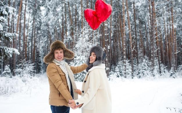 Casal de inverno apaixonado. menino e menina abraçando na neve do inverno e a floresta de fadas com balões.