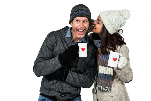 Casal de inverno apreciando bebidas quentes