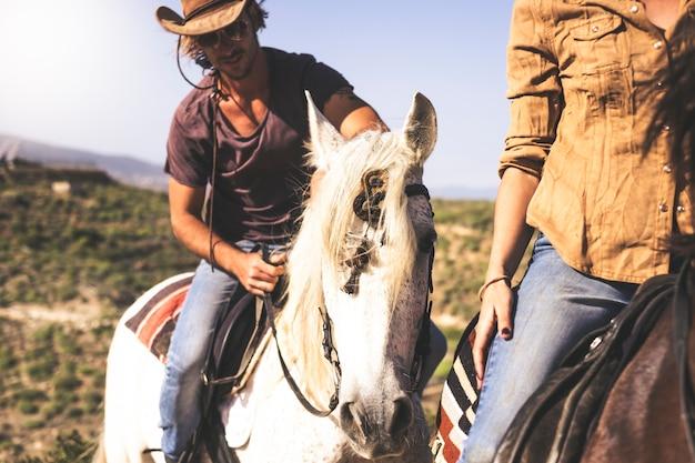 Casal de jovem alternativo milenar e mulher cavalgando na natureza - atividade de lazer ao ar livre para pessoas bonitas com animais