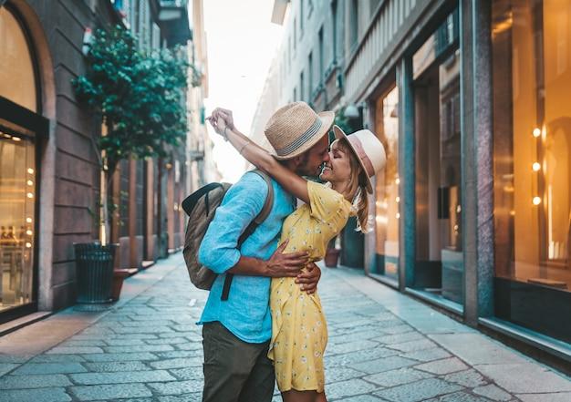 Casal de jovem turista apaixonado, tendo um beijo romântico na cidade.