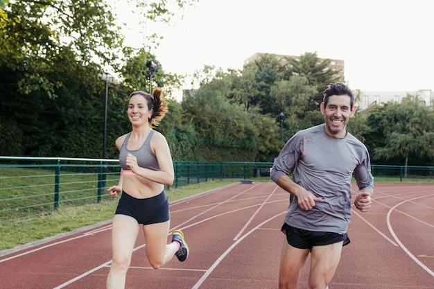 Casal de jovens adultos correndo juntos