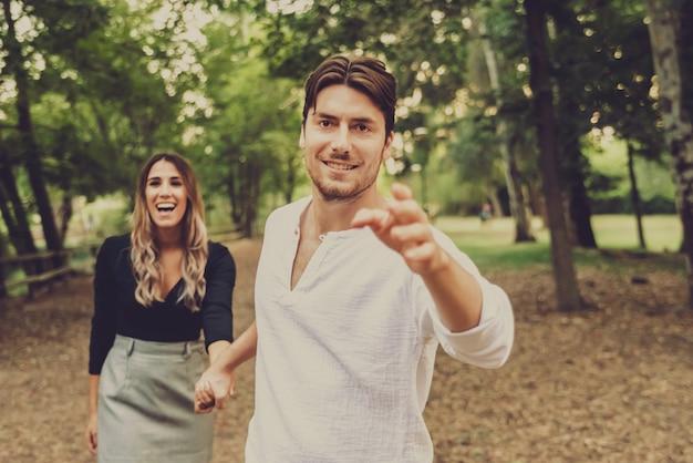 Casal de jovens amantes passeando sem pressa pelo campo.