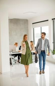 Casal de jovens empresários caminhando juntos no espaço do escritório