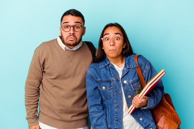 Casal de jovens estudantes de raça mista isolado em fundo azul encolhe os ombros e abre os olhos confusos.