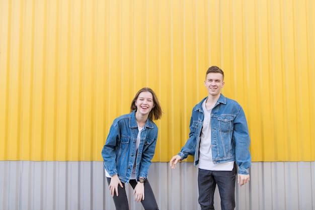 Casal de jovens felizes sobre fundo de parede amarela. menina e homem em fundo amarelo a sorrir.