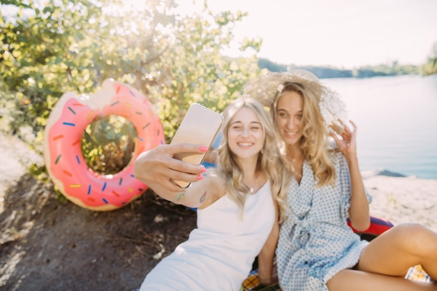 Casal de jovens lésbicas se divertindo à beira do rio em dia de sol