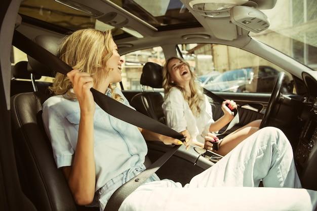Casal de jovens lésbicas se preparando para uma viagem de férias no carro em um dia ensolarado