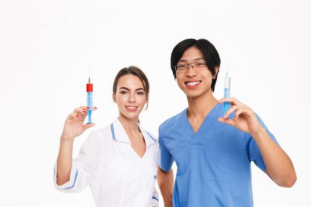 Casal de jovens médicos multiétnicos confiantes usando uniforme em pé, isolado na parede branca, mostrando seringas
