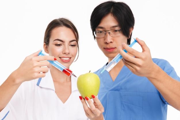 Casal de jovens médicos multiétnicos confiantes, vestindo uniforme, em pé, isolado na parede branca, injetando líquido em uma maçã