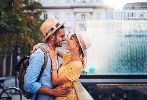 Casal de jovens turistas apaixonados dando um beijo romântico na cidade
