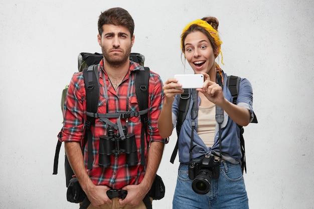 Casal de jovens turistas com equipamento