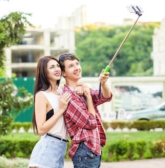Casal de jovens turistas felizes tirando uma selfie com smartphone no monopé na cidade que o homem está