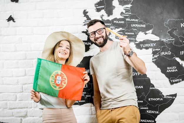 Casal de jovens viajantes em pé com bandeira portuguesa perto da parede com mapa-múndi, sonhando com as férias de verão em portugal