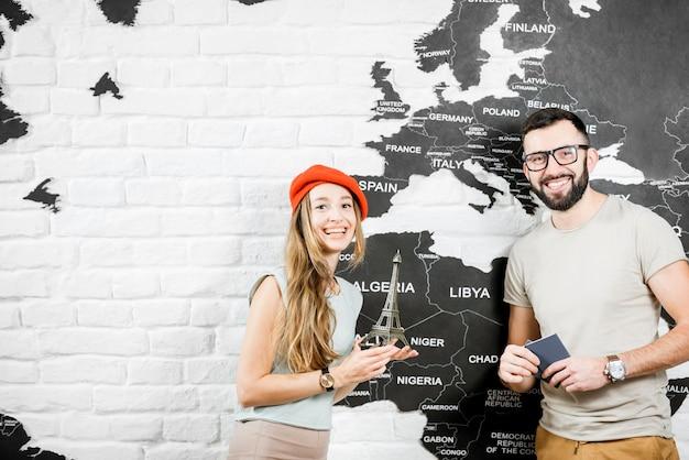 Casal de jovens viajantes em pé perto da parede com mapa-múndi, sonhando com as férias de verão em paris