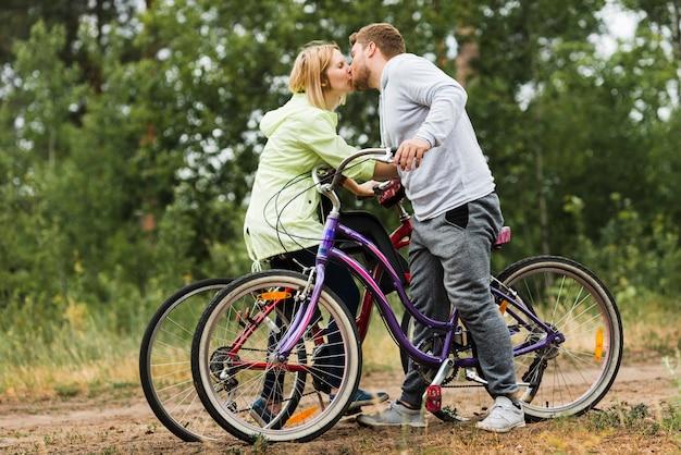 Casal de lateral beijando em bicicletas
