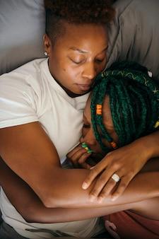 Casal de lésbicas a aninhar-se a dormir na cama