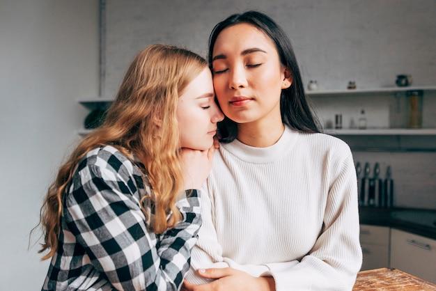 Casal de lésbicas abraçando com os olhos fechados