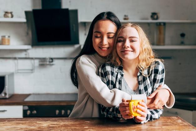 Casal de lésbicas abraçando enquanto bebe chá na cozinha