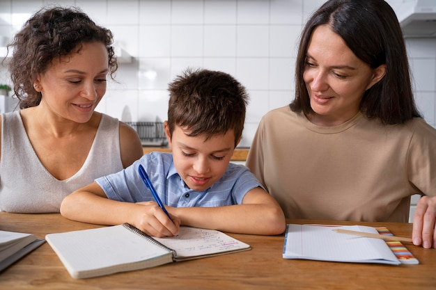 Casal de lésbicas ajudando o filho a fazer o dever de casa