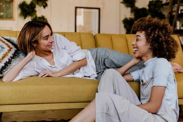 Casal de lésbicas alegres conversando em uma sala de estar