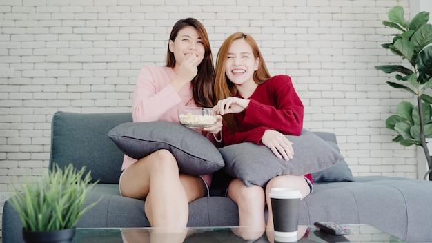 Casal de lésbicas asiáticos assistindo tv rir e comendo pipoca na sala de estar em casa, doce casal desfrutar