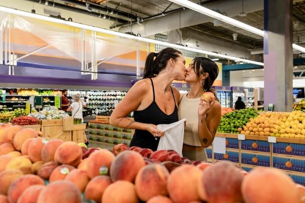 Casal de lésbicas brincalhonas fazendo compras, se beijando em um supermercado