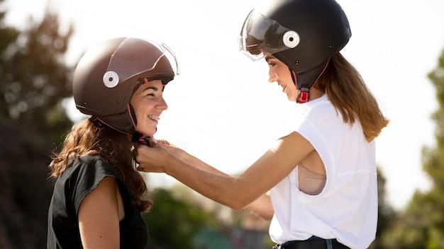 Casal de lésbicas colocando capacetes para uma viagem de moto