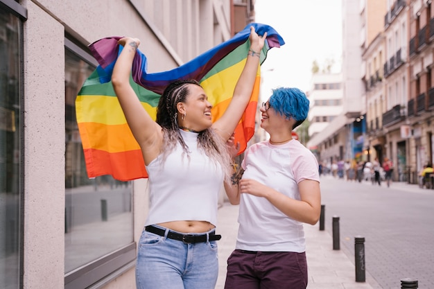 Casal de lésbicas com atitude divertida, mostrando orgulhosamente uma bandeira de lgbt de orgulho.