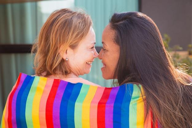 Casal de lésbicas com bandeira lgbt de volta à câmera beijando esquimó. dia dos namorados