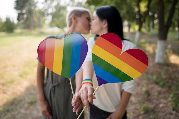 Casal de lésbicas com bandeira lgbt em formato de coração