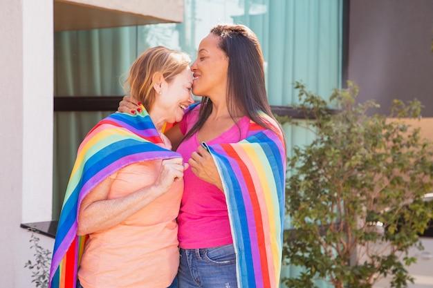 Casal de lésbicas com bandeira lgbt. esposa beijando sua esposa na testa. dia dos namorados