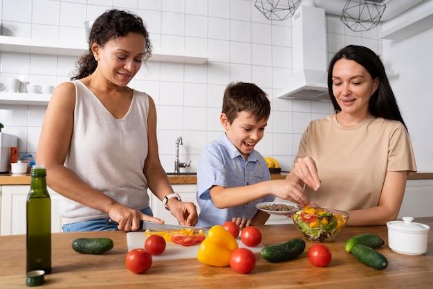 Casal de lésbicas com o filho preparando comida