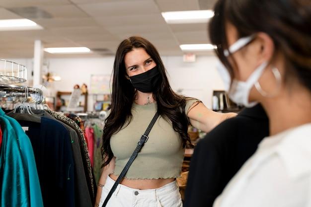 Casal de lésbicas comprando roupas, loja de moda sustentável