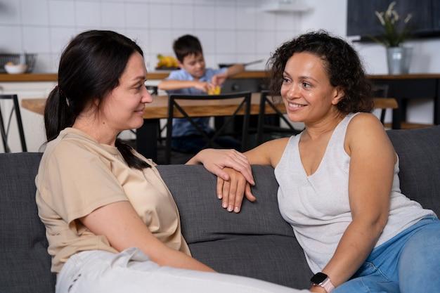 Casal de lésbicas conversando enquanto o filho está fazendo a lição de casa