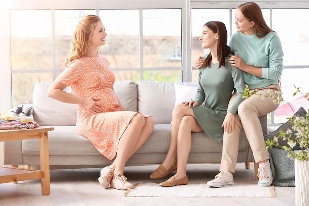Casal de lésbicas e mulher grávida em casa. conceito de maternidade substituta