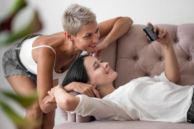 Casal de lésbicas em casa tirando selfie