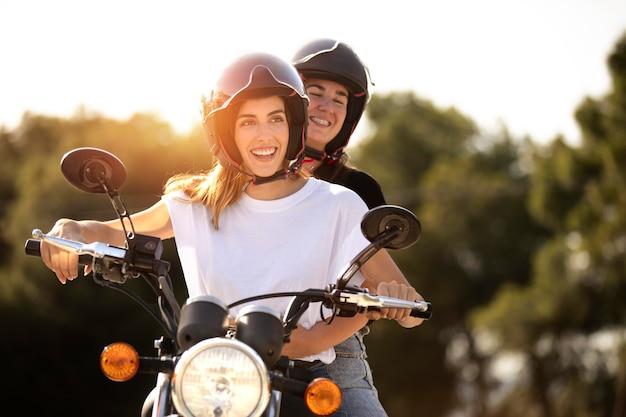 Casal de lésbicas em uma motocicleta com capacetes