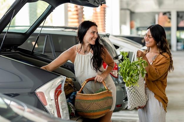 Casal de lésbicas fazendo compras, colocando coisas no porta-malas do carro