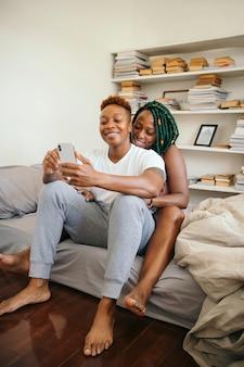 Casal de lésbicas feliz brincando no telefone