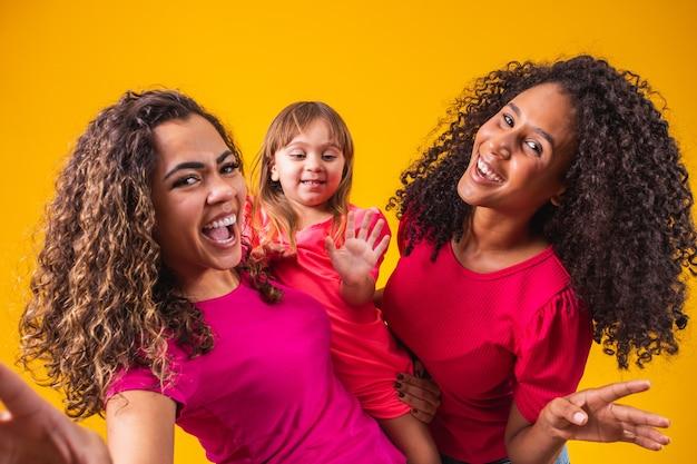 Casal de lésbicas feliz com a garotinha adotada na cor de fundo