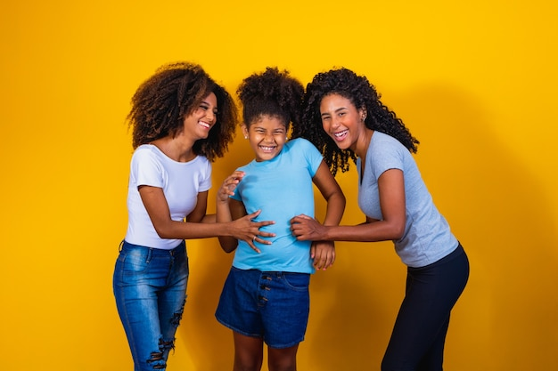Casal de lésbicas feliz com criança em fundo amarelo. casal com filha adotiva, conceito de adoção