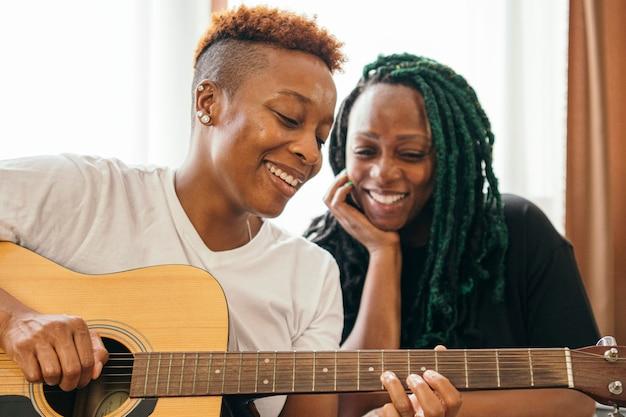 Casal de lésbicas feliz curtindo tocar música