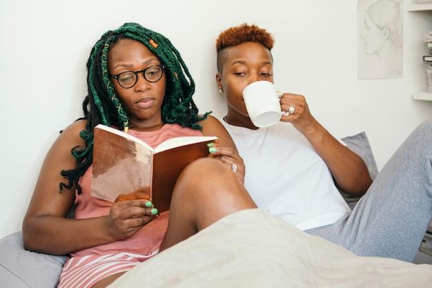 Casal de lésbicas feliz lendo um livro e tomando café