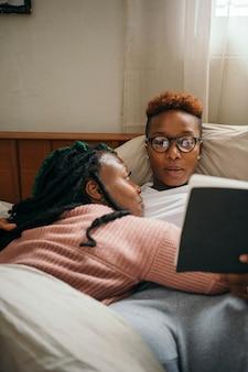 Casal de lésbicas feliz se abraçando e lendo um livro