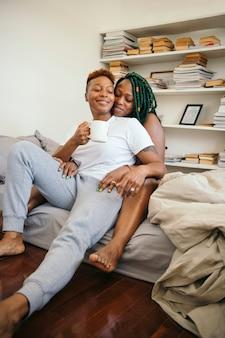 Casal de lésbicas feliz se abraçando e tomando café