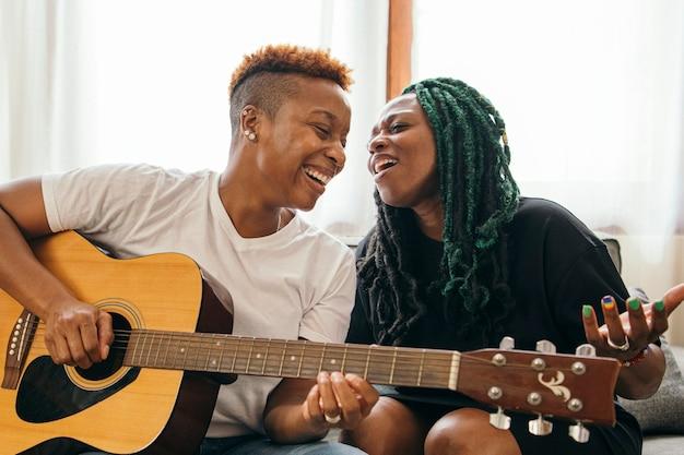 Casal de lésbicas feliz tocando violão e cantando